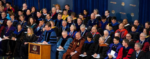 Faculty seated on stage wearing academic robes at University ceremony.